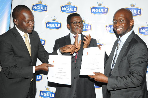 L-R: Mr.Ronald Kawadwa,Chief Executive Officer Majestic Brands Limited ,Oweek:Charles Peter Mayiga,Prime Minister of Buganda and Mr.Alvin Mbugua,Managing Director Uganda Breweries Limited exchanging contracts of the royalty partnership.